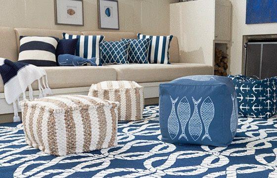 nautical striped pouf ottoman cushions on blue and white rope rug Coastal living room ideas