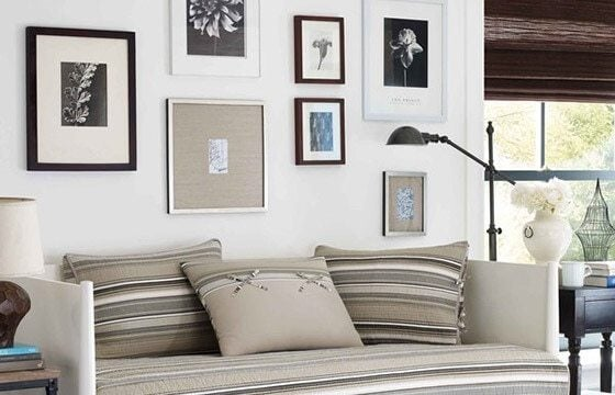 A coastal gallery wall hung on a wall in a coastal bedroom - Coastal Furniture and Decor Ideas