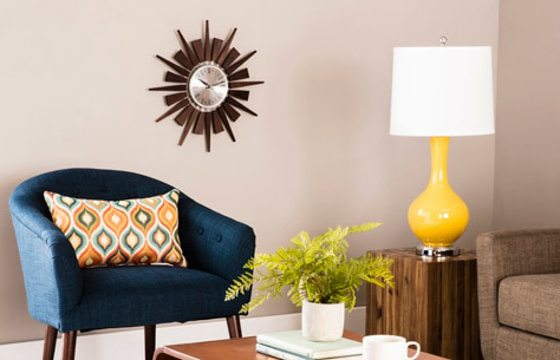 A blue chair and yellow lamp add a pop of color to this Mid-Century Modern living room