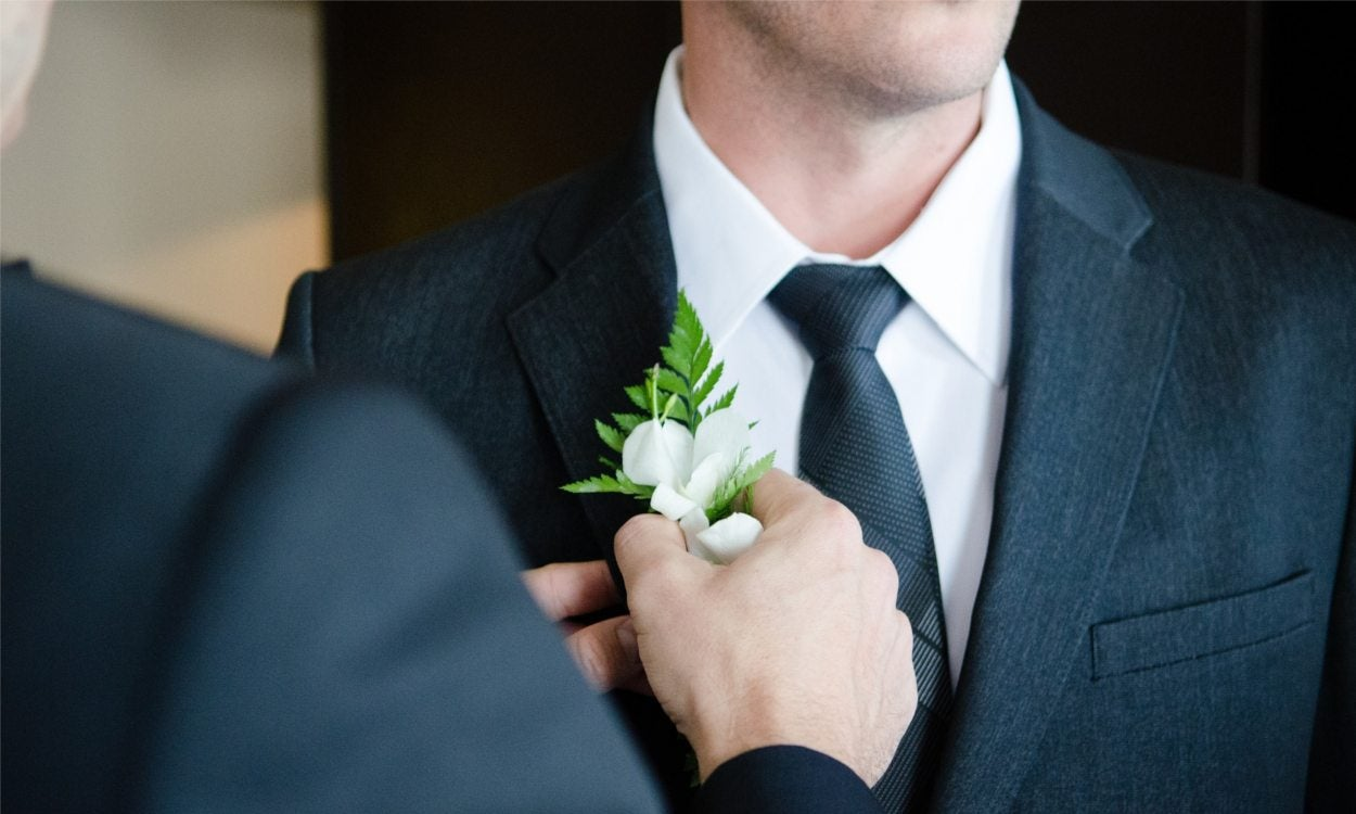 a man in a suit with a flower pinned on his lapel
