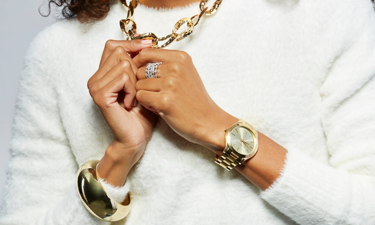 A woman wearing both gold and silver jewelry
