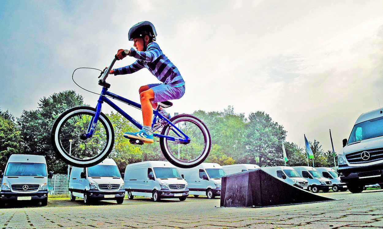 Kid riding a bike off of a ramp