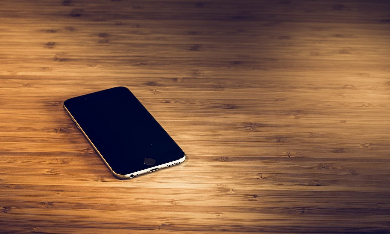 a black cell phone on a wood surface