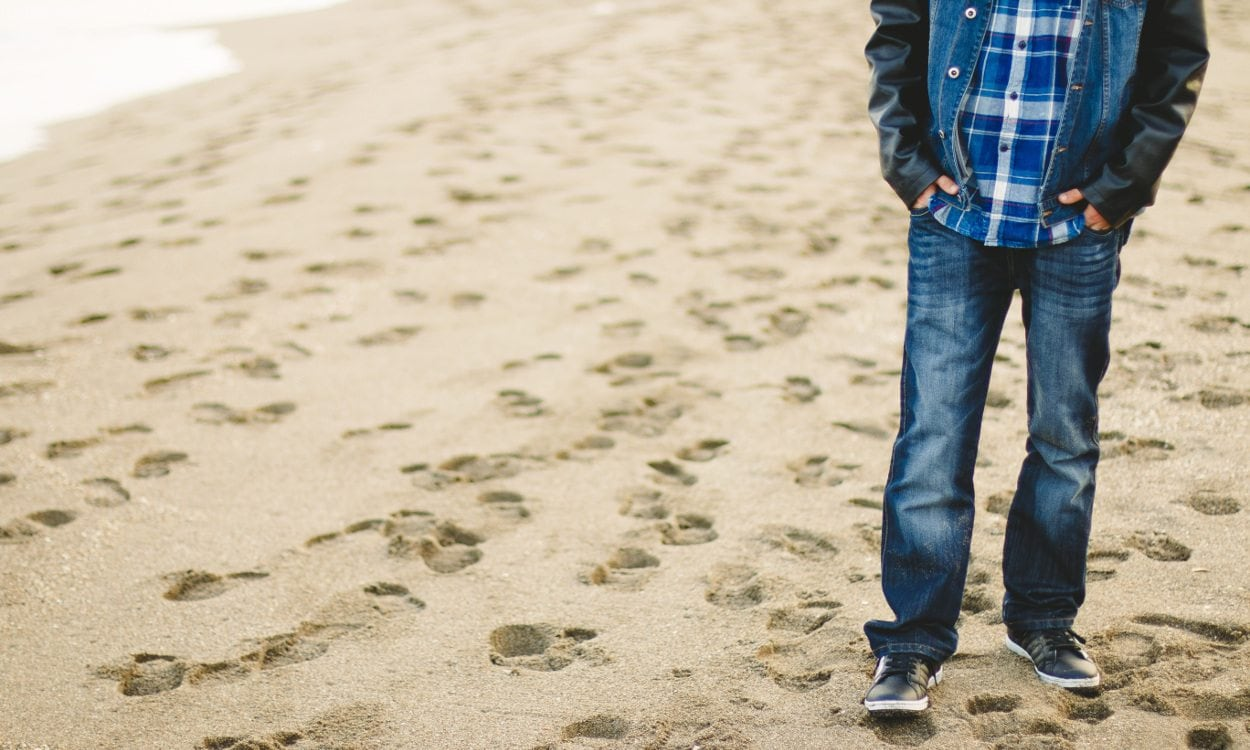 Man wearing jeans on beach Men's Jeans Buying Guide