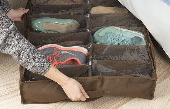 A woman placing shoe storage under her bed