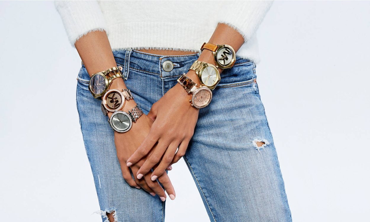 A woman wearing a stack of watches that are perfect for Christmas 2017