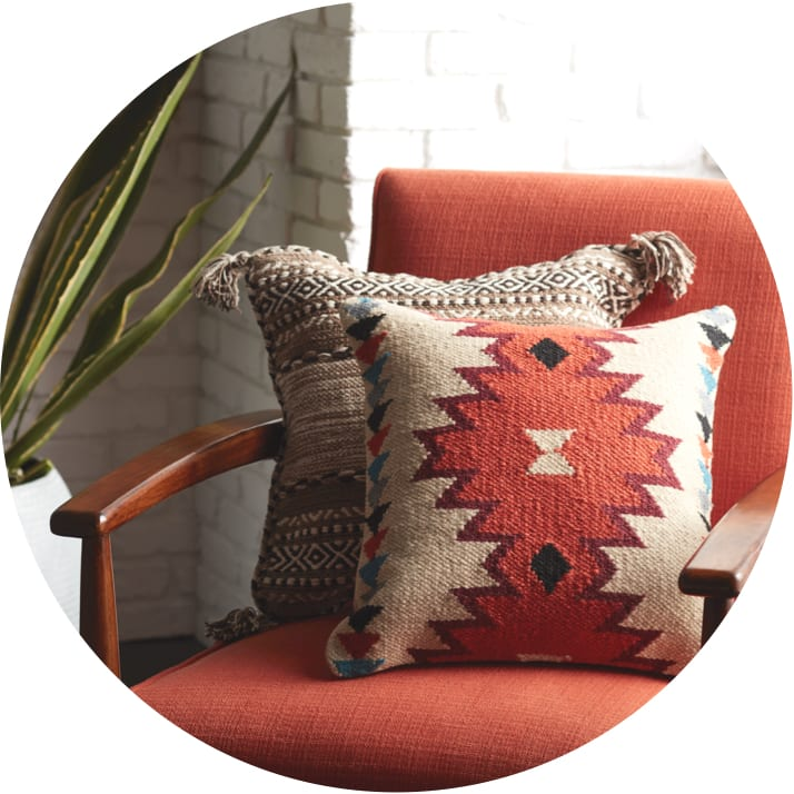 A boho accent chair an throw pillows, perfect christmas gift ideas for the free- spirited boho on your list
