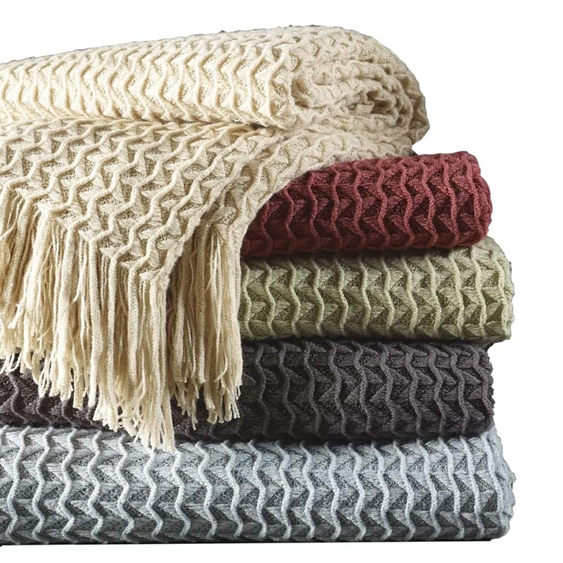 A stack of cozy throw blankets- an essential for a reading nook