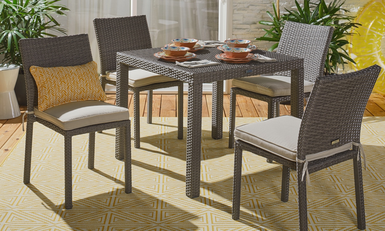 Outdoor patio furniture on a yellow outdoor rug