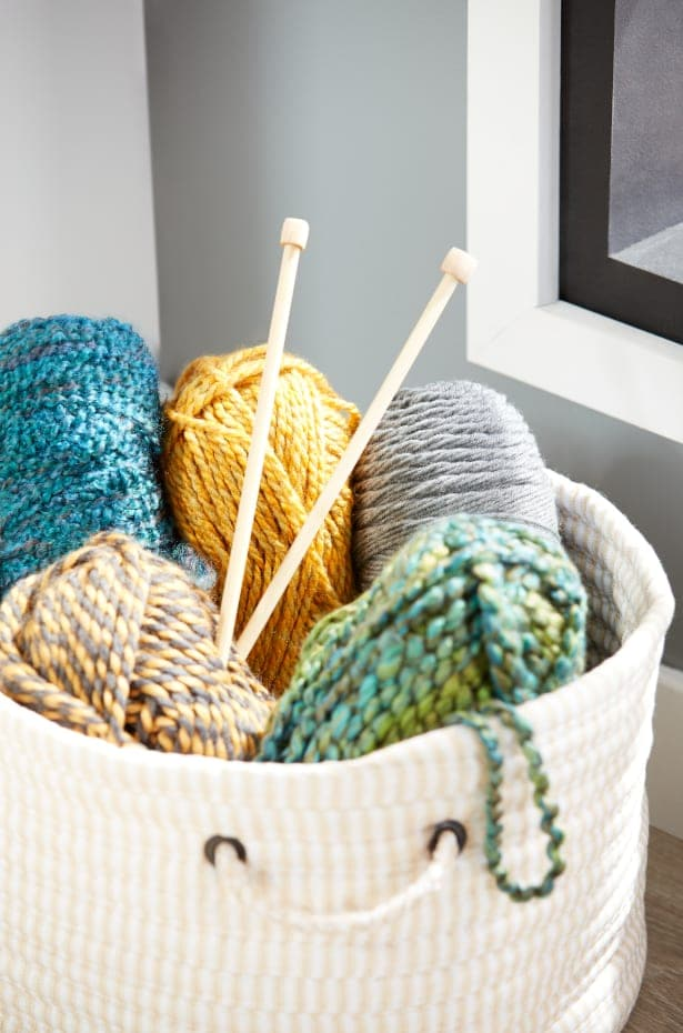 Knitting needles and yarn in a basket.
