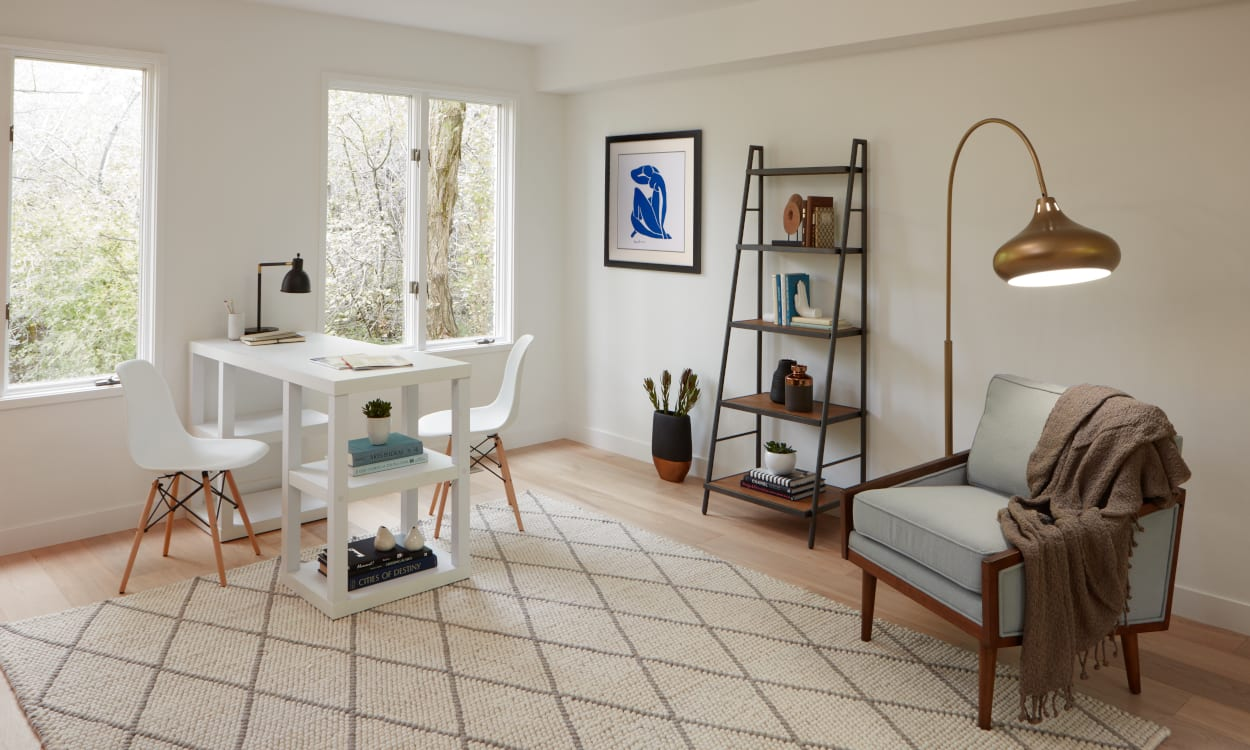 Home office with a white desk, bookcase, and arm chair
