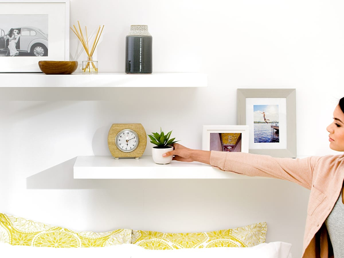 Woman placing a small succulent onto a white floating shelf