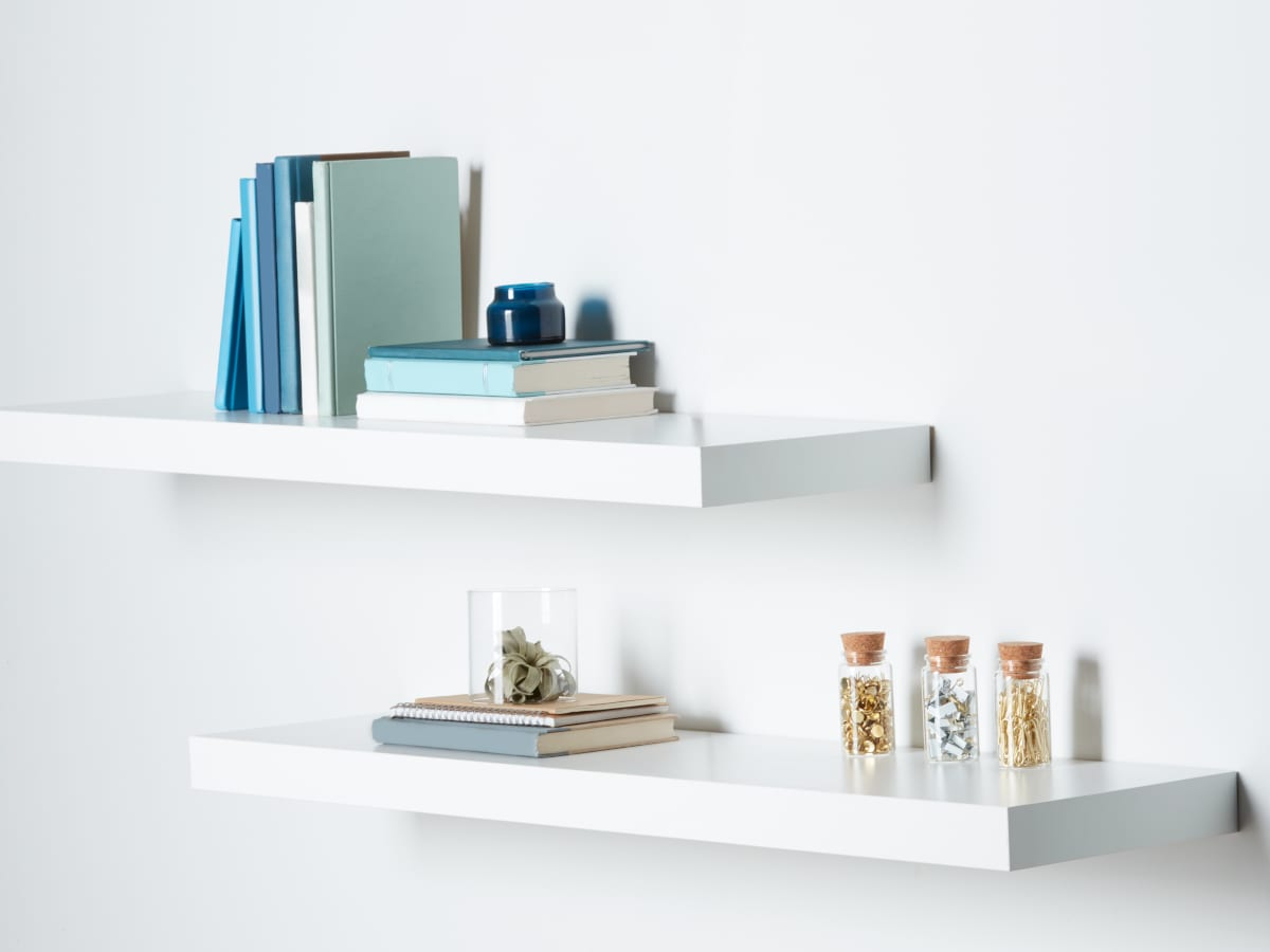 Two White Floating Shelves With Blue Books and Other Decor