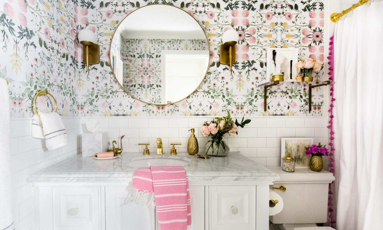 Small bathroom with floral wallpaper, a white vanity, and brass sconces.
