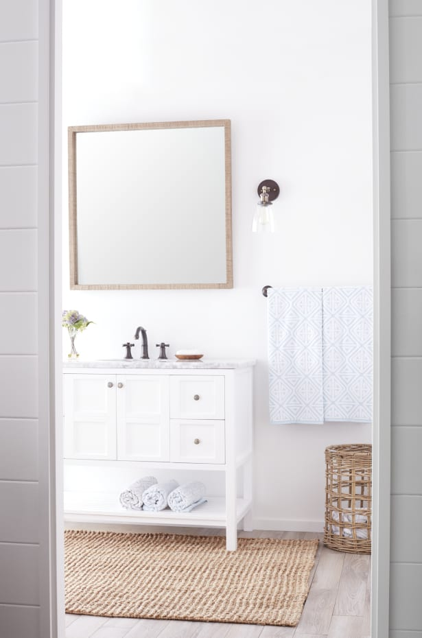 Wood frame mirror above a white vanity in a small bathroom.