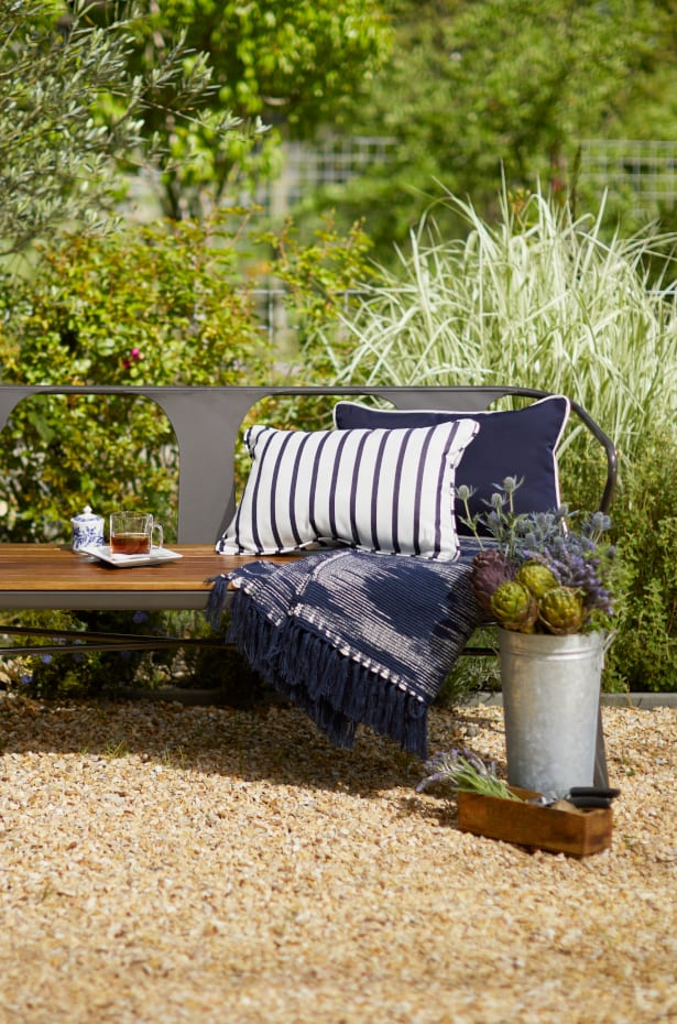 Outdoor patio with a metal pot and metal bench.