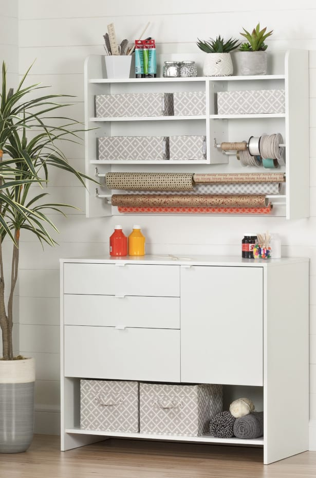 White craft room organizer with dowels to hang ribbon.