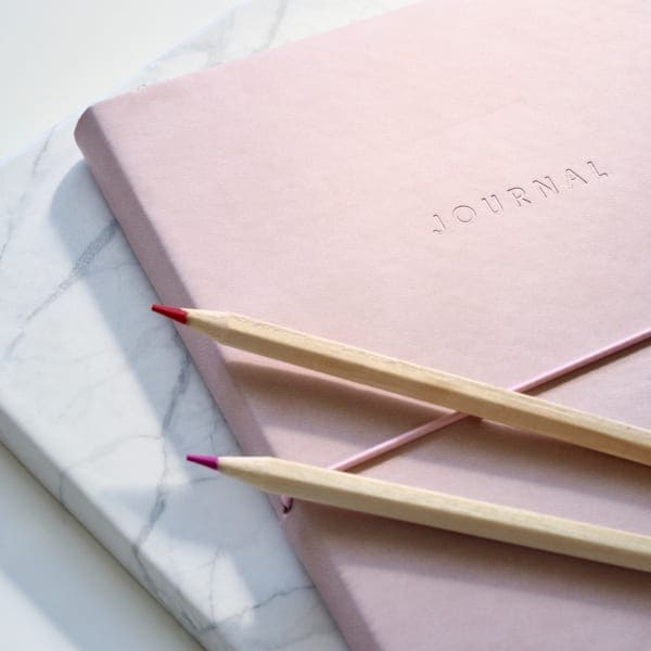 Pink and white journal with pencils.