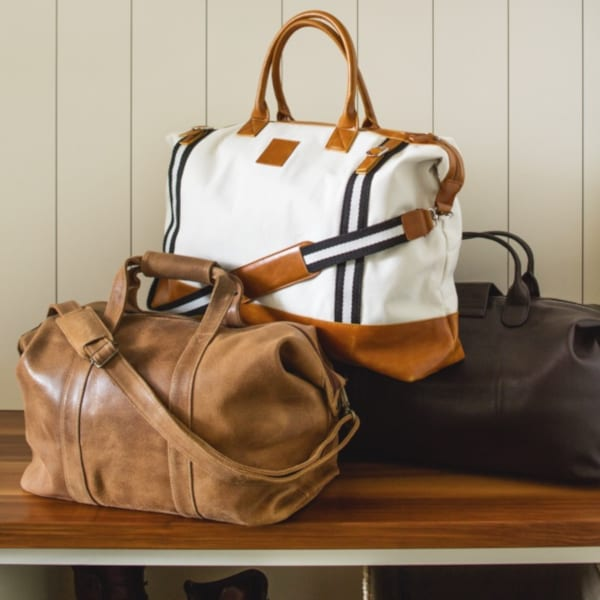 Tan leather, white linen, and black leather weekend bags.
