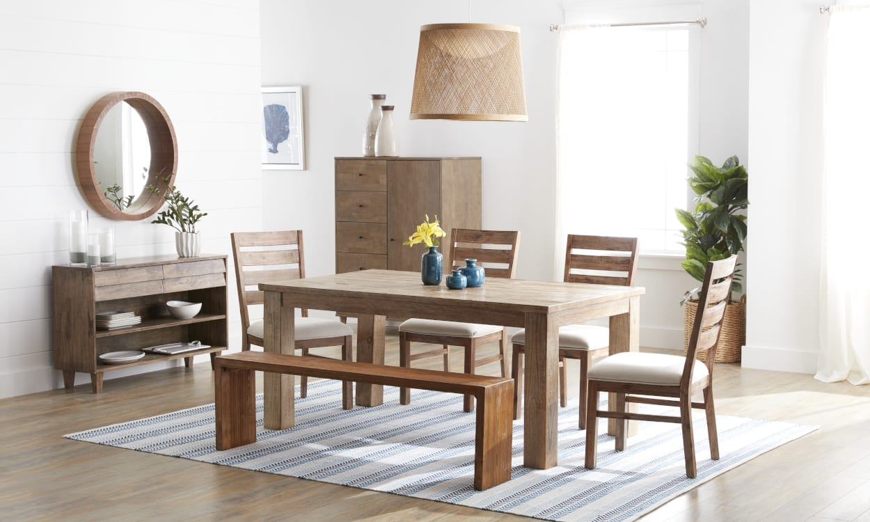 Dining room with a blue stripped rug on a light wood floor