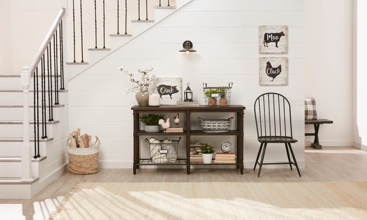 Farmhouse entryway with a neutral rug that matches the wood flooring