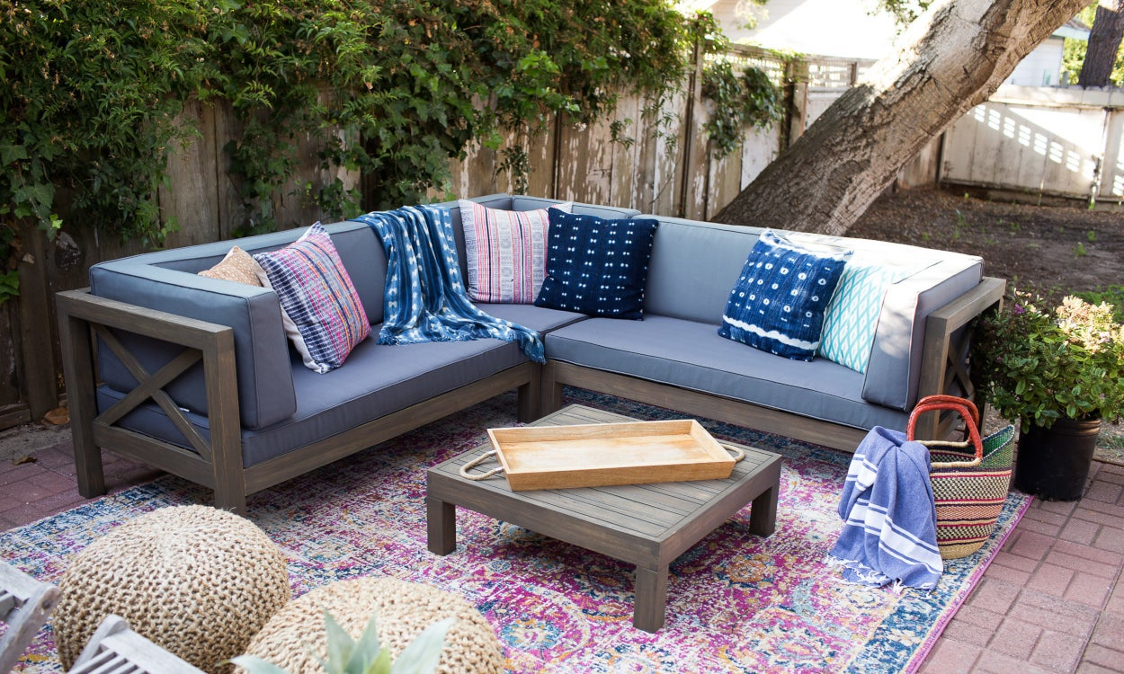 Patio designed with a colorful rug and throw pillows