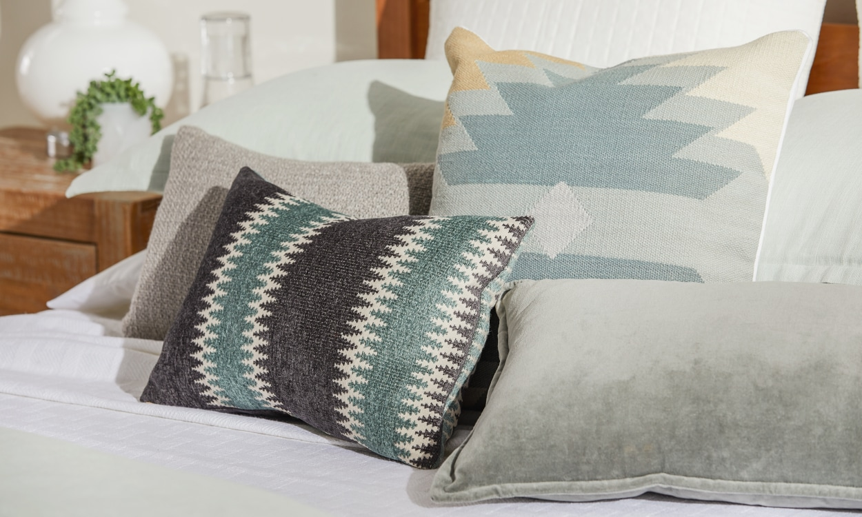 Blue patterned throw pillows set on a bed.