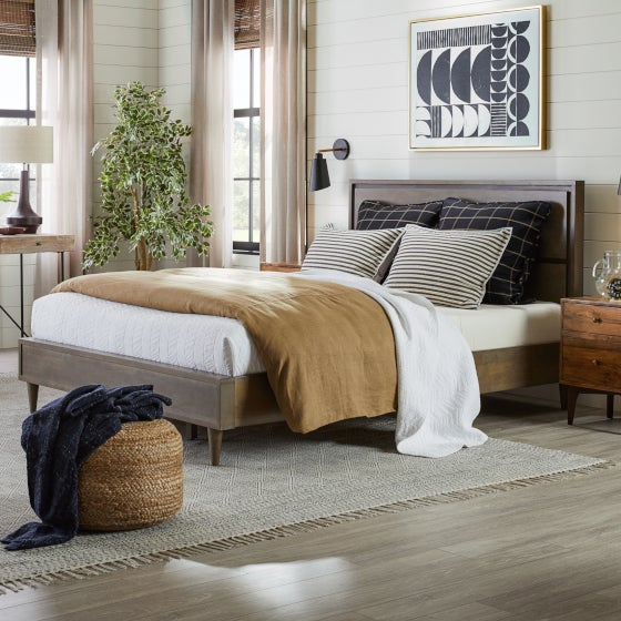 A bedroom with just the bed on the area rug