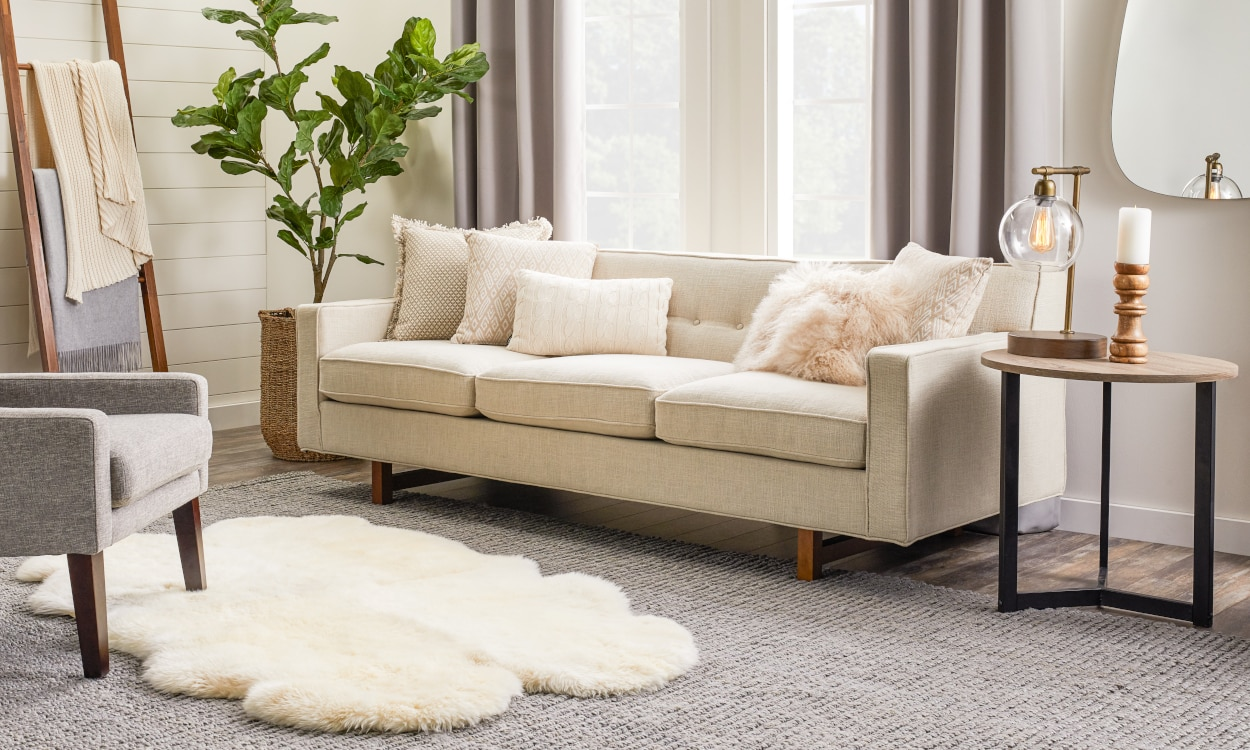 Faux fur rug layered over a gray jute rug in a living room