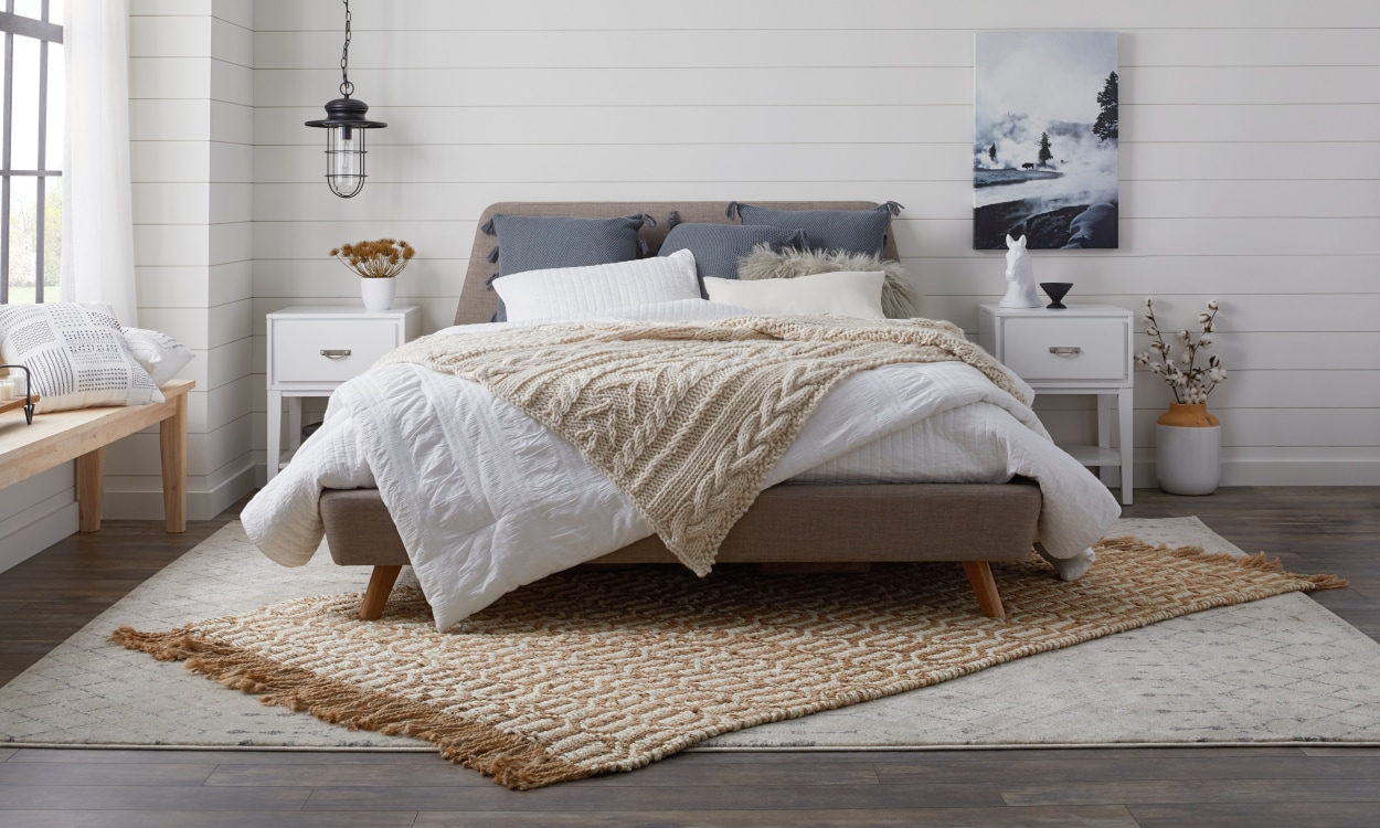 Jute rug layered diagonally on a gray patterned rug in a bedroom