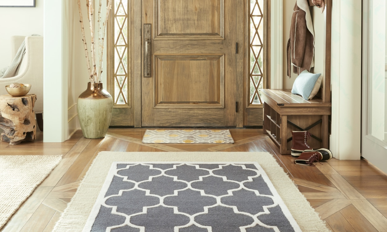 Blue patterned runner rug layered on a cream runner rug in an entryway