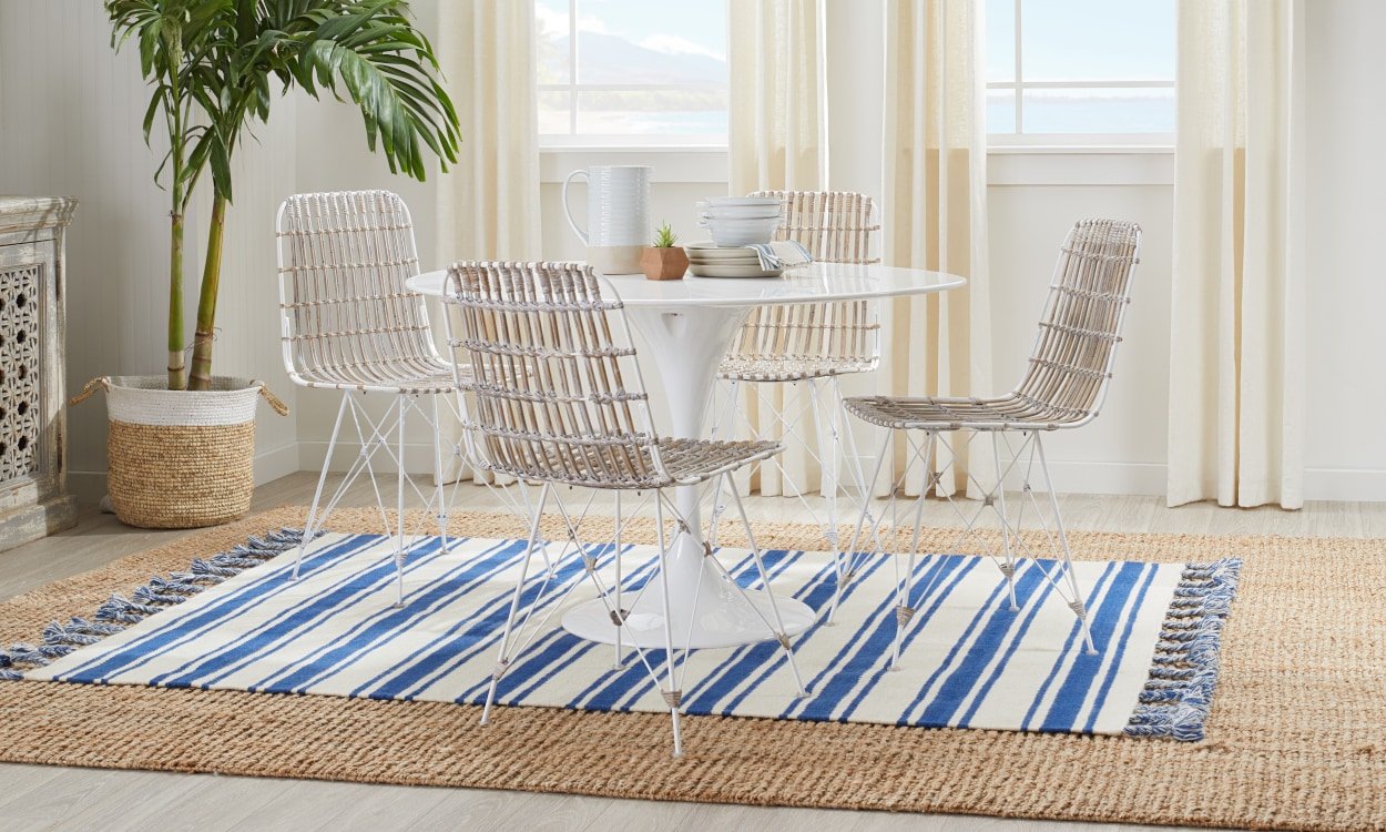 Smaller blue striped rug layered on a larger jute rug