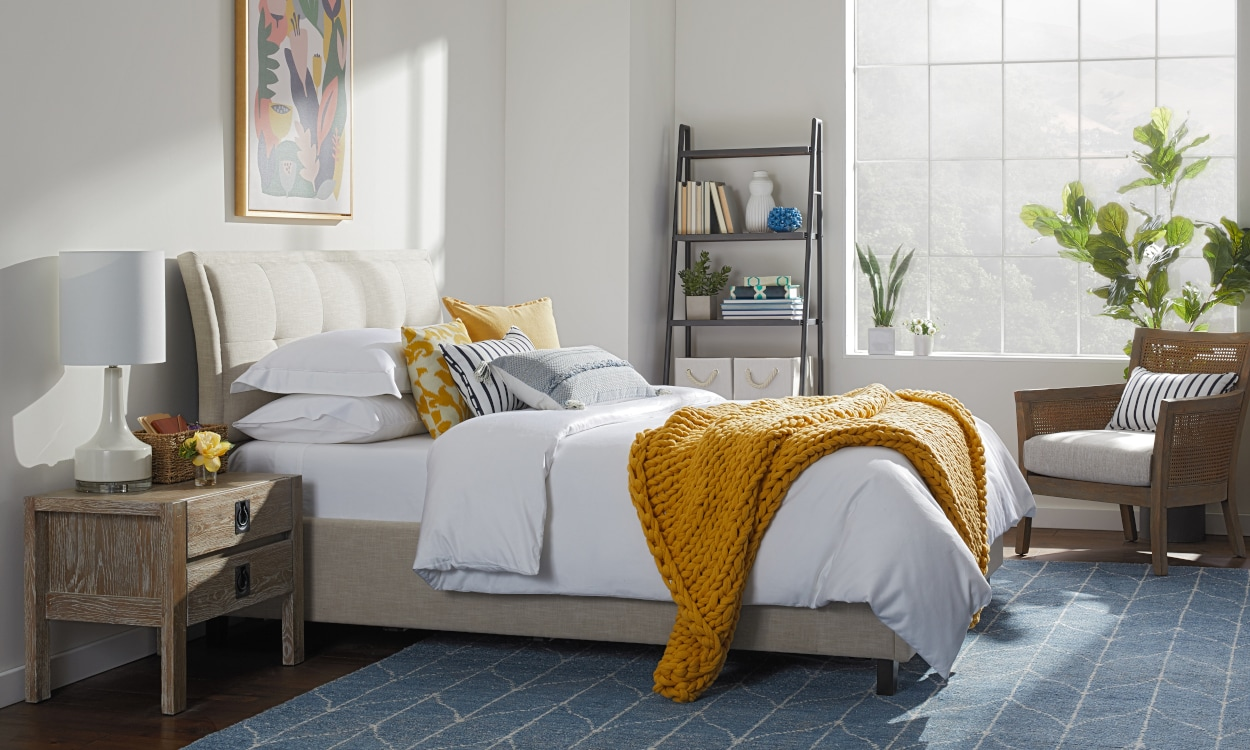 Bedding trends: printed throw pillows styled on a white comforter. Bedding 101