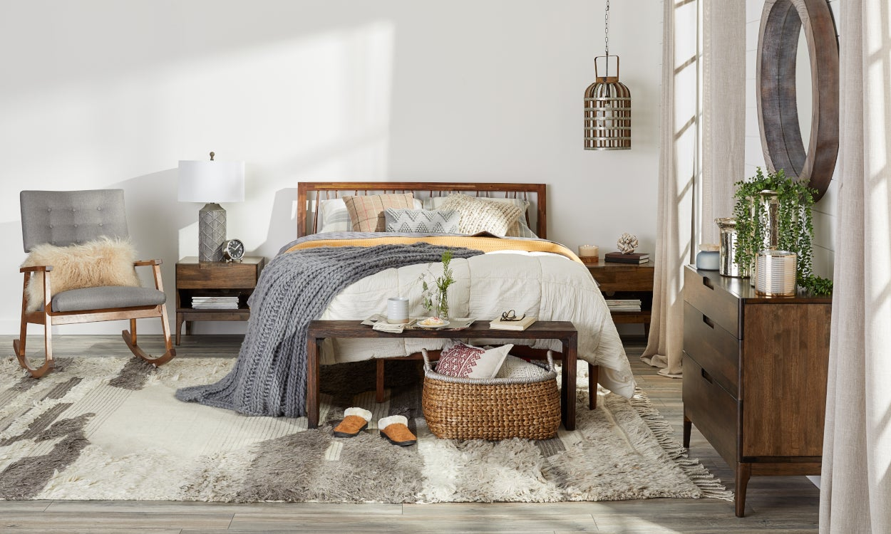 Winter bedding: a down comforter, knit blankets, and flannel sheets styled on a bed