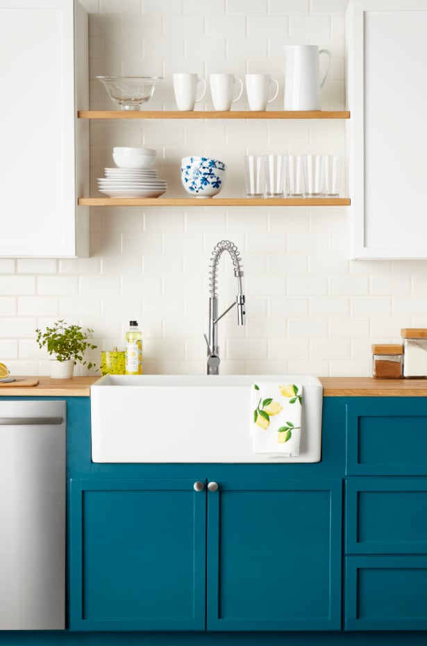 Apron sink in kitchen with blue cabinets
